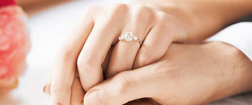 Woman holding her fiance's hand with an oval diamond ring on her finger in Swartz Creek, MI